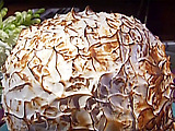 Brown Sugar Baked Alaska with Chocolate-Hazelnut Ice Cream, Flaming Frangelico-Rum Sauce, and Candied Hazelnuts