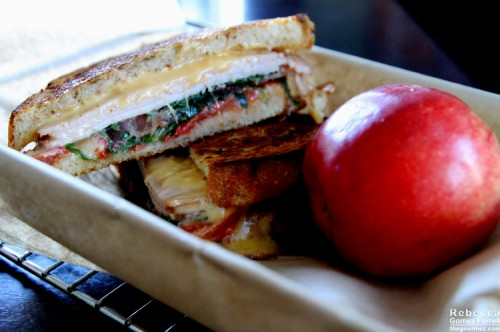Club with cheddar, havarti, smoked turkey, roasted tomatoes, bacon, stout mustard, and arugula on sourdough.