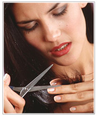 Woman cutting ends of hair.