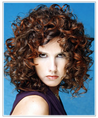 Model with brown curly hair and copper highlights