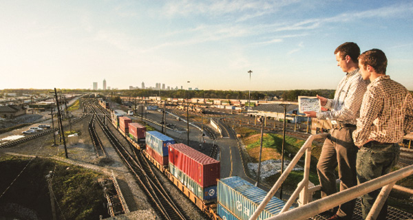 Two businessmen overlook a train loaded with intermodal containers