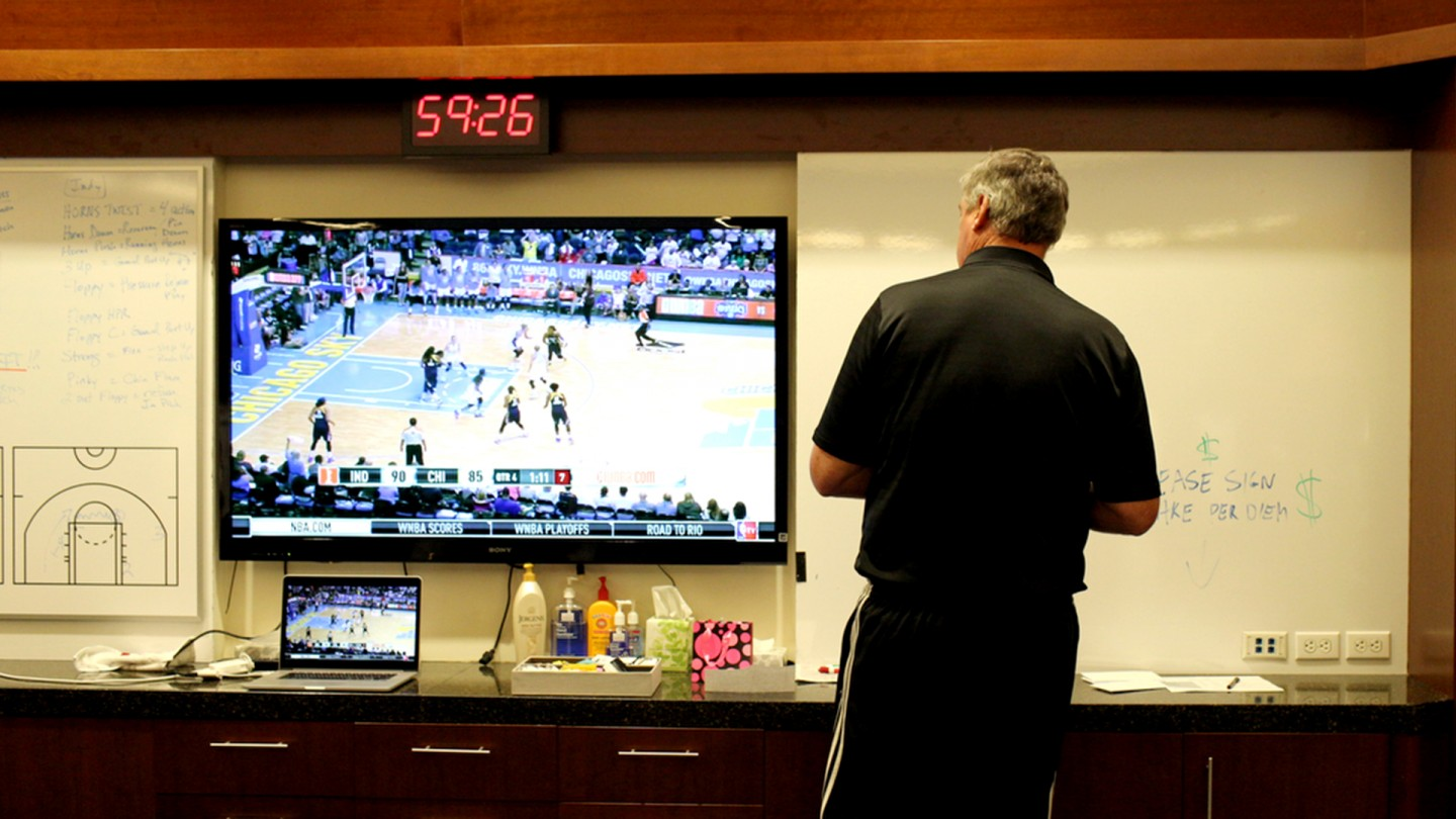 Coach Bill Laimbeer writes on the white board in the locker room while watching game footage.