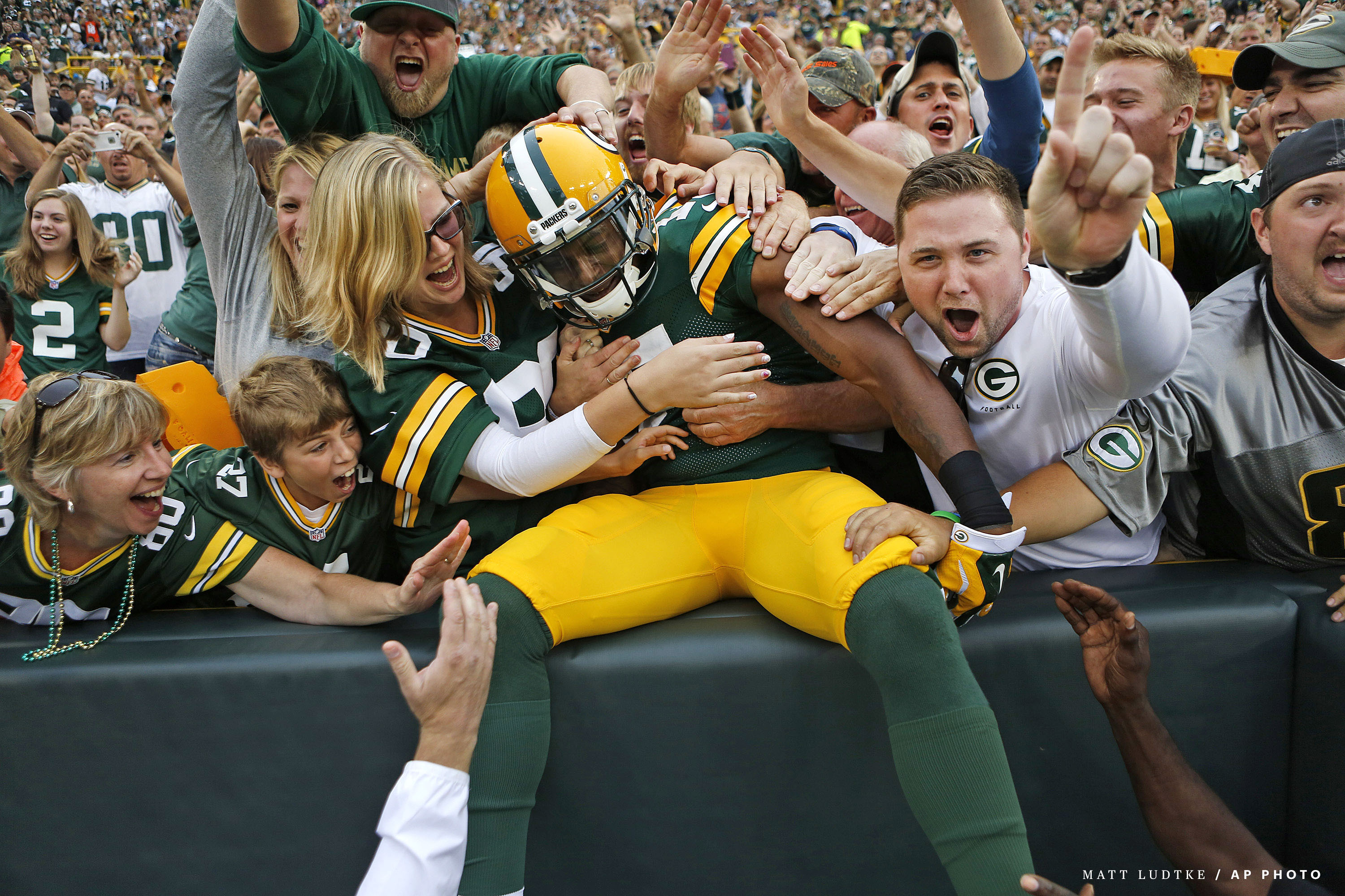 Green Bay Packers wide receiver Davante Adams leaps into the stands after scoring a touchdown against the Kansas City Chiefs during an NFL pre-season football game Thursday Aug. 28, 2014, in Green Bay, Wis. (AP Photo/Matt Ludtke)