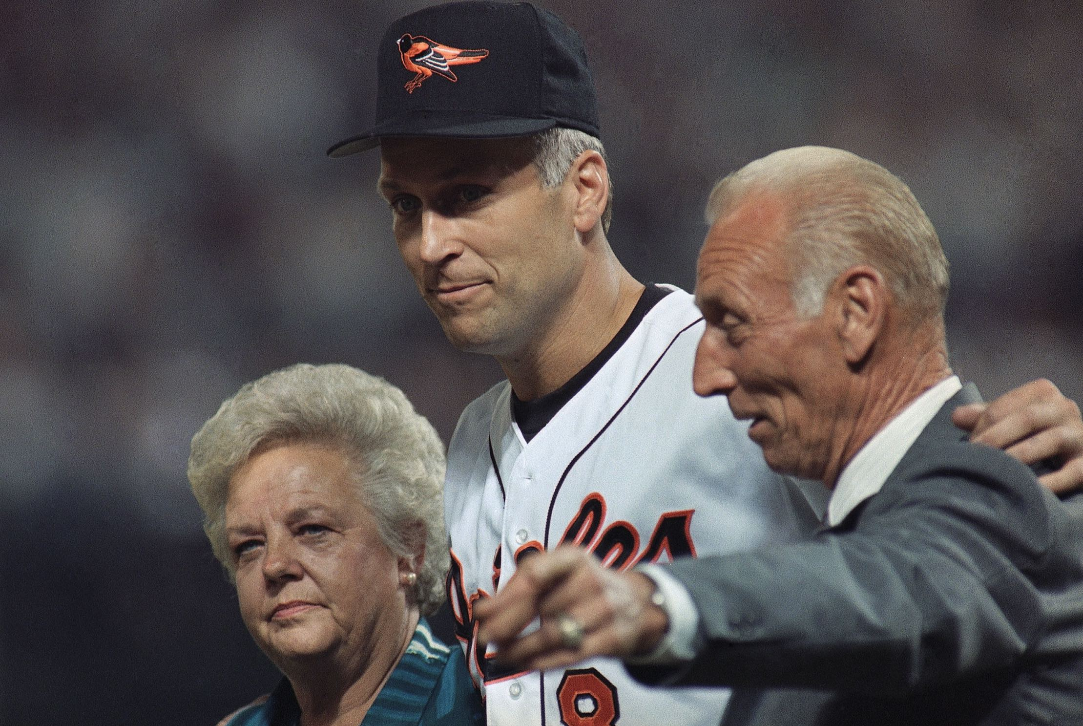 Baltimore Orioles shortstop Cal Ripken, Jr., center, walk onto the field with his parent Violet and Cal Ripken Sr. for post game ceremonies Wednesday, Sep 6,1995 at Baltimore. Ripken broke Lou Gehrig's record of 2,130 consecutive games Wednesday as Orioles beat the California Angeles 4-2. (AP Photo/Denis Paquin)