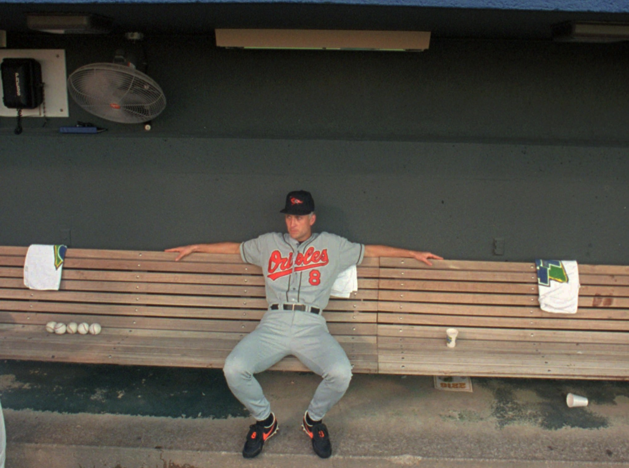 Baltimore Orioles Cal Ripken has the dugout bench to himself before a ceremonial gift exchange at Kauffman Stadium Friday, June 14, 1996, in Kansas City, Mo. Ripken will break the world baseball record when he plays his 2,216th consecutive game. (AP Photo/Cliff Schiappa)