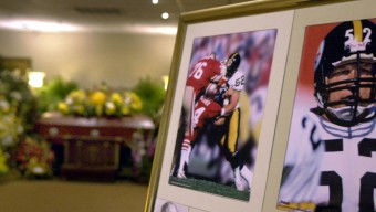 The casket bearing the body of former Pittsburgh Steelers center Mike Webster at left is surrounded by flowers and photographs of the Hall-of-Fame lineman after funeral services in a Pittsburgh funeral home Friday, Sept. 27, 2002. Webster died Tuesday. (AP Photo/Keith Srakocic)