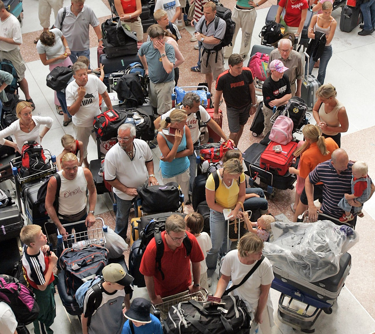 Western tourist, mostly all from Sweden, line up to check in for a flight home at Phuket International airport Saturday, Jan. 1, 2005.  The death toll in Thailand from last week?s tsunami is over 4,800, more than half of those are foreigners with an additional 6,000 still missing.  (AP Photo/David Longstreath)