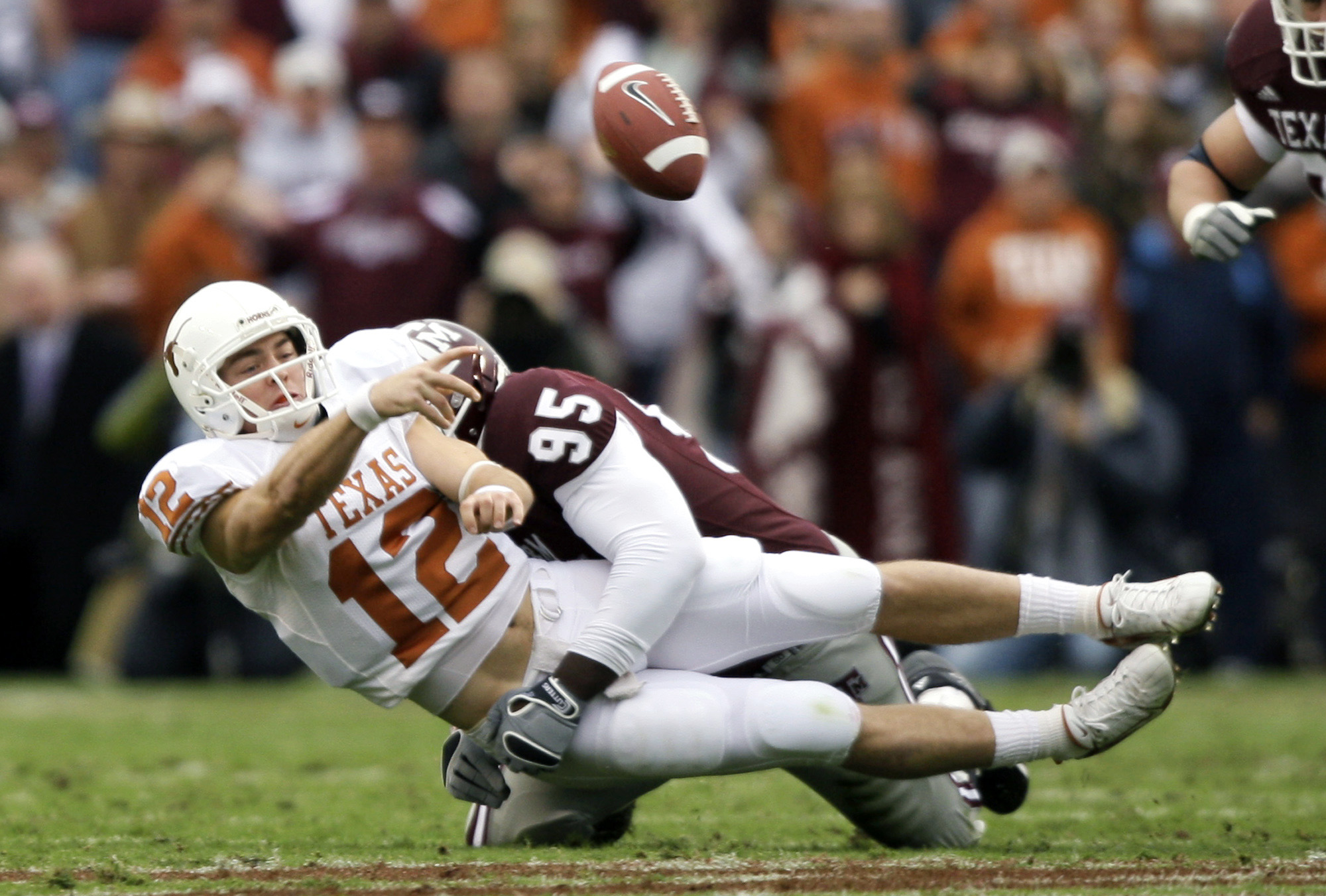 Texas quarterback Colt McCoy (12) throws an incomplete pass as he is hit by Texas A&M's Henry Smith (95) during the first quarter of a football game Friday, Nov. 23, 2007 in College Station, Texas.  (AP Photo/David J. Phillip)