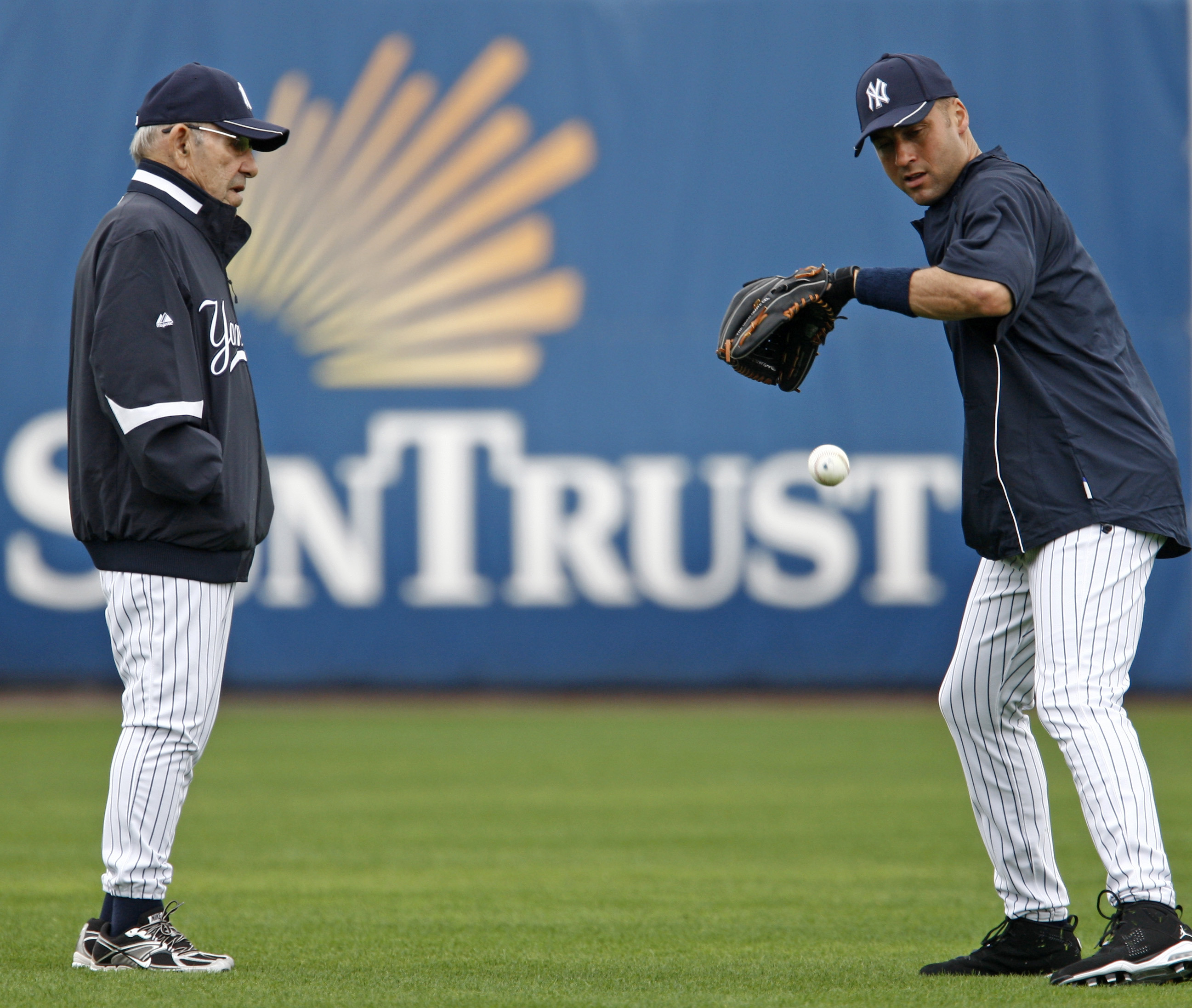 New York Yankees special adviser Yogi Berra, left, watches shortstop Derek Jeter field a ball as the Yankees full squad worked out during baseball spring training at Steinbrenner Field in Tampa, Fla., Wednesday, Feb. 24, 2010.  (AP Photo/Kathy Willens)
