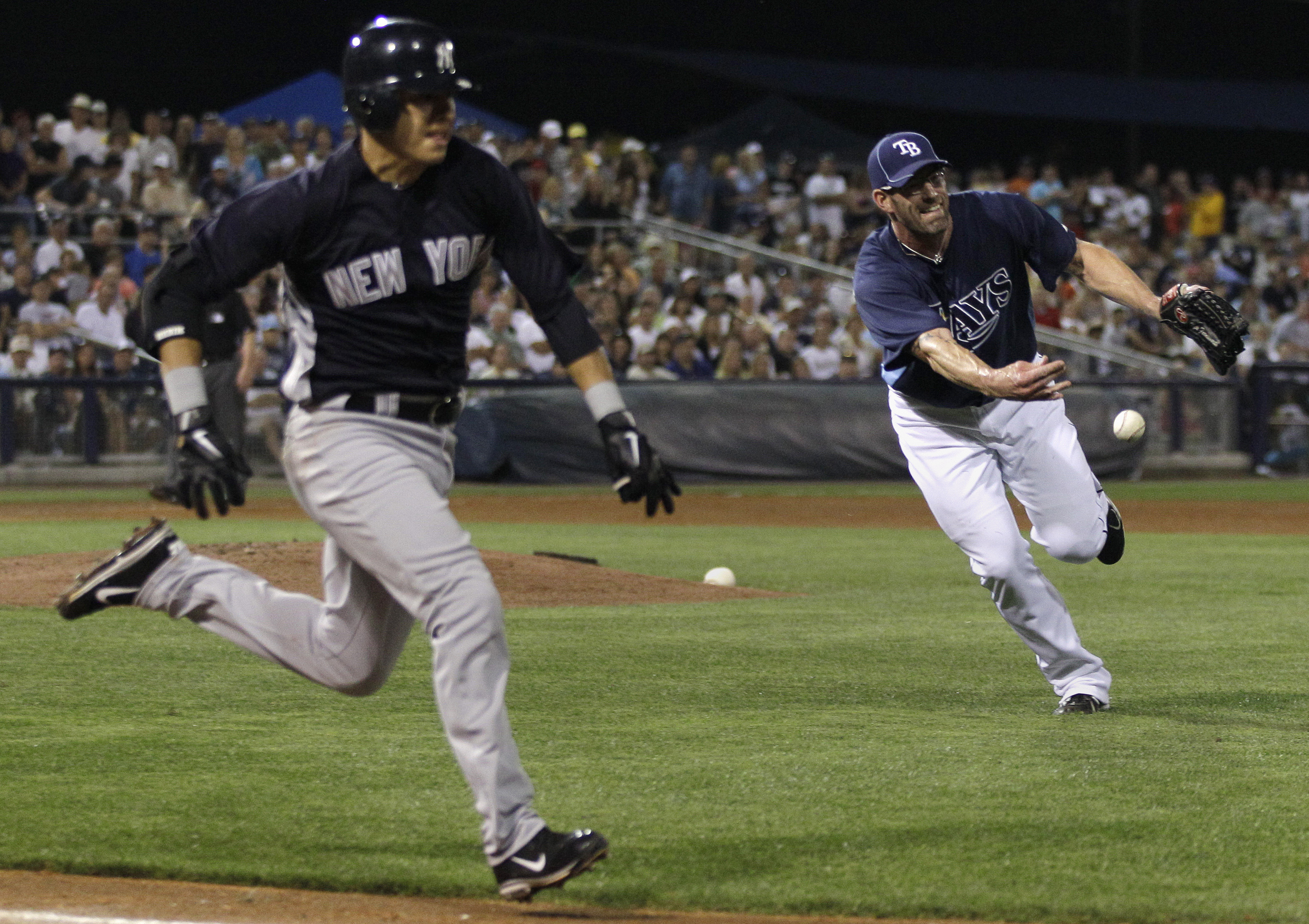 Tampa Bay Rays pitcher Kyle Farnsworth, right, flips the ball to first baseman Dan Johnson on a sacrifice bunt by New York Yankees Ramiro Pena in the fifth inning of a spring training baseball game in Port Charlotte, Fla., Monday, March 21, 2011. (AP Photo/Charles Krupa)