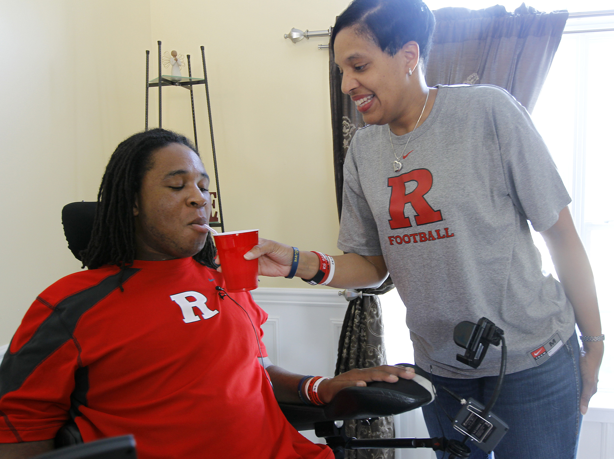Eric LeGrand, left, gets a drink from his aunt Cheryl Curet, Monday, April 25, 2011 in Jackson, N.J. LeGrand, a Rutgers defensive tackle who was paralyzed from the neck down in a game against Army in 2010, was recently released from the Kessler Institute for Rehabilitation in West Orange, N.J. (AP Photo/Julio Cortez)
