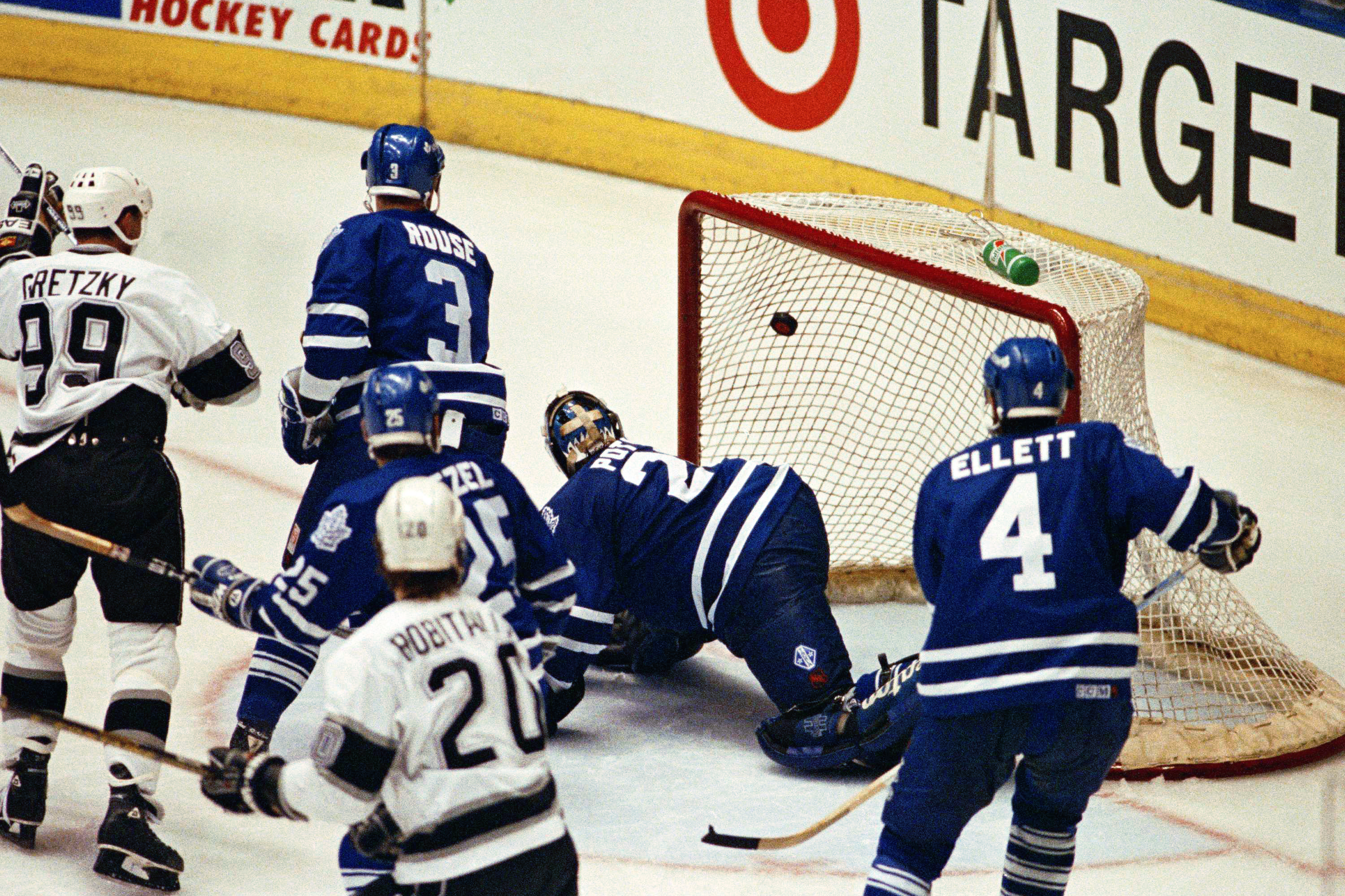 Toronto Maple Leafs goalie Felix Potvin watches Los Angeles King's Wayne Gretzky's shot go into the net for the game-winning goal in sudden-death overtime to tie the seven game series at three games apiece on Wednesday, May 27, 1993 in Inglewood, Calif., at Forum. The final score was 5-4. Gretzky teammate Luc Robitaille (20), who assisted in the scoring effort, also watches along with a pair Maple Leaf players. (AP Photo/Mark J. Terrill)