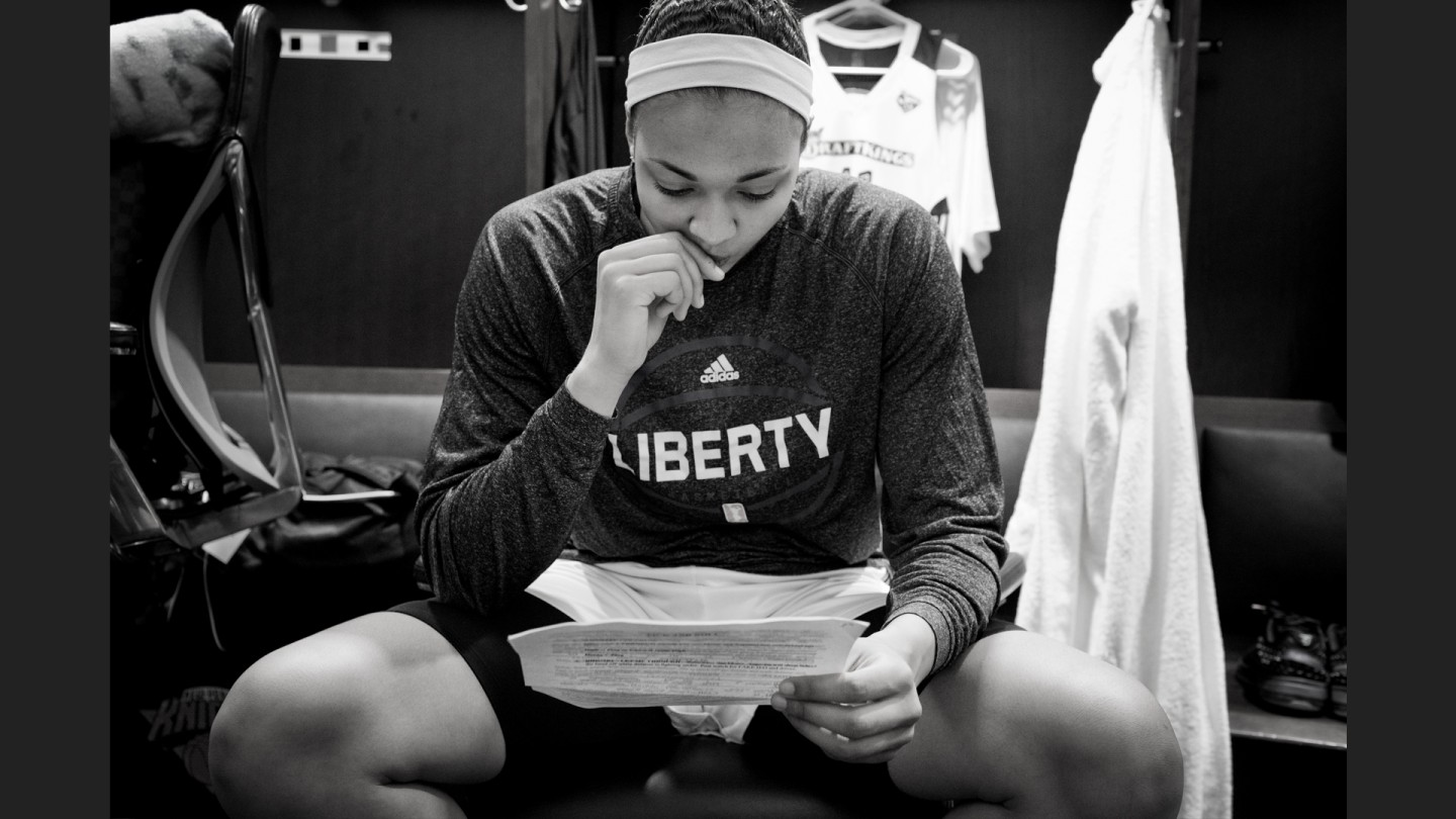 Kiah Stokes reads over game notes and stats before the game.