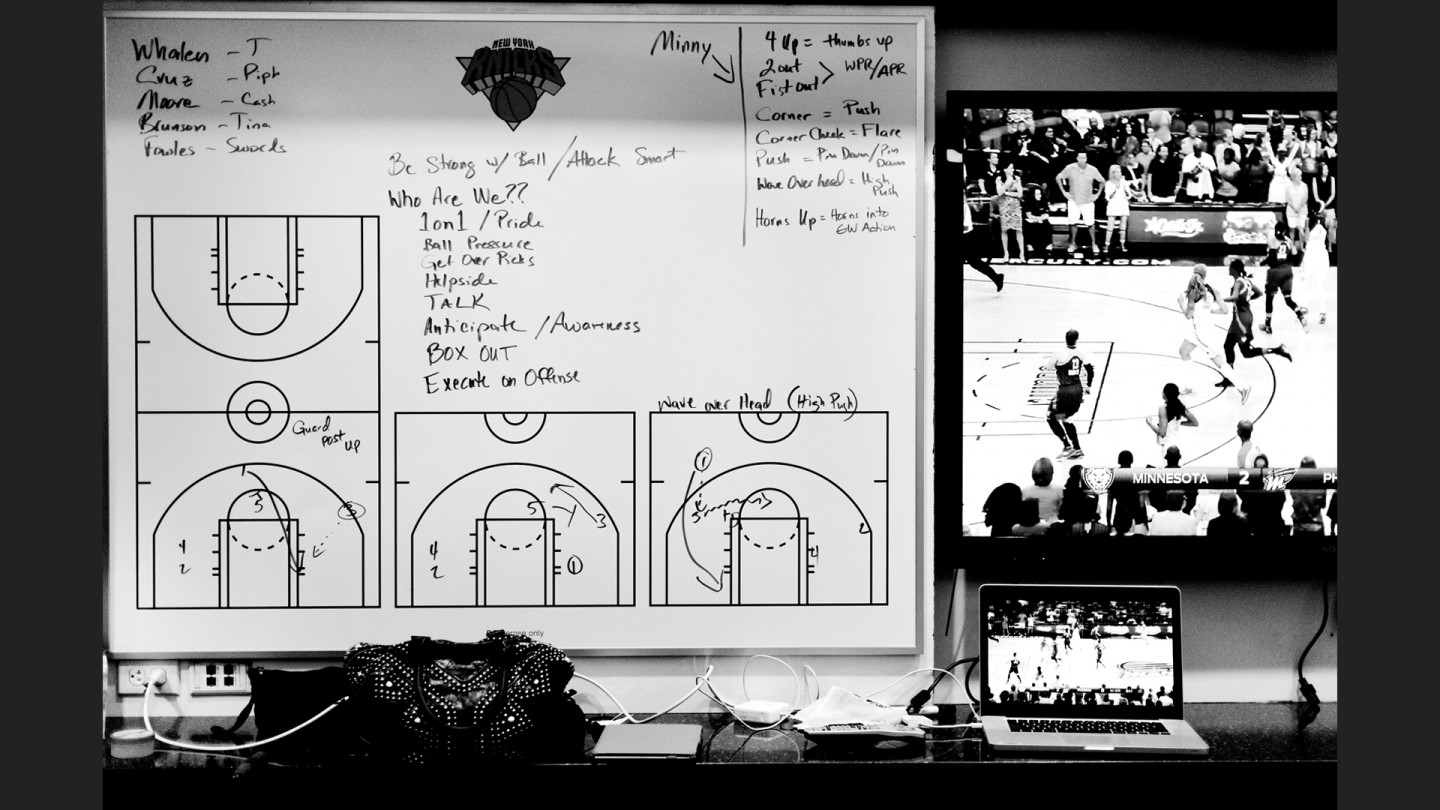 The team reviews both game footage and strategy in the locker room.
