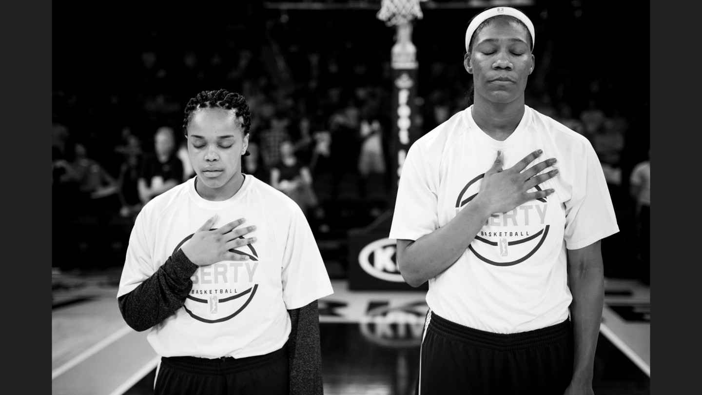 Brittany Boyd and Avery Warley-Talbert put their hands over their hearts during the National Anthem.