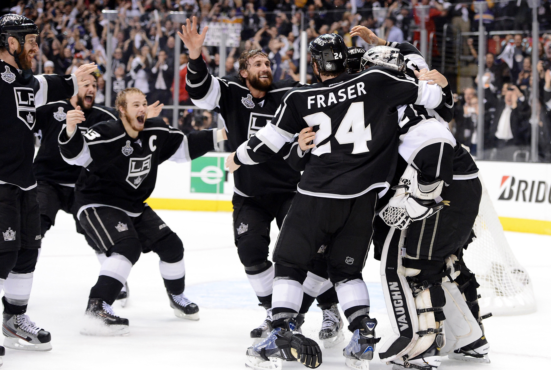 LOS ANGELES, CA - JUNE 11: (L-R) Rob Scuderi #7, Alec Martinez #27, captain Dustin Brown #23, Jarret Stoll #28, Colin Fraser #24, Drew Doughty #8 of the Los Angeles Kings surround goaltender Jonathan Quick #32 of the Los Angeles Kings after winning Game Six of the 2012 Stanley Cup Final 6-1 to win the series 4-2 at Staples Center on June 11, 2012 in Los Angeles, California. (Photo by Harry How/Getty Images)