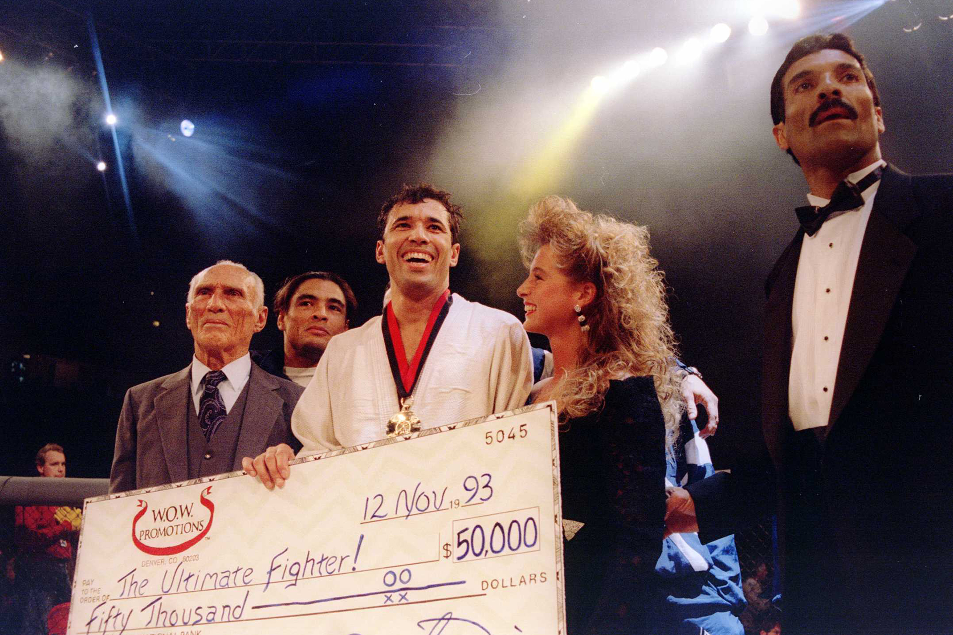 "Jiu-Jitsu black belt Royce Gracie (USA) receives a $50,000 check after becoming ""The Ultimate Fighter"" by defeating Gerard Gordeau of the Netherlands int he finals of the Ultimate Fighter Championships in Denver, Colorado.  Mandatory Credit: Markus Boesch"