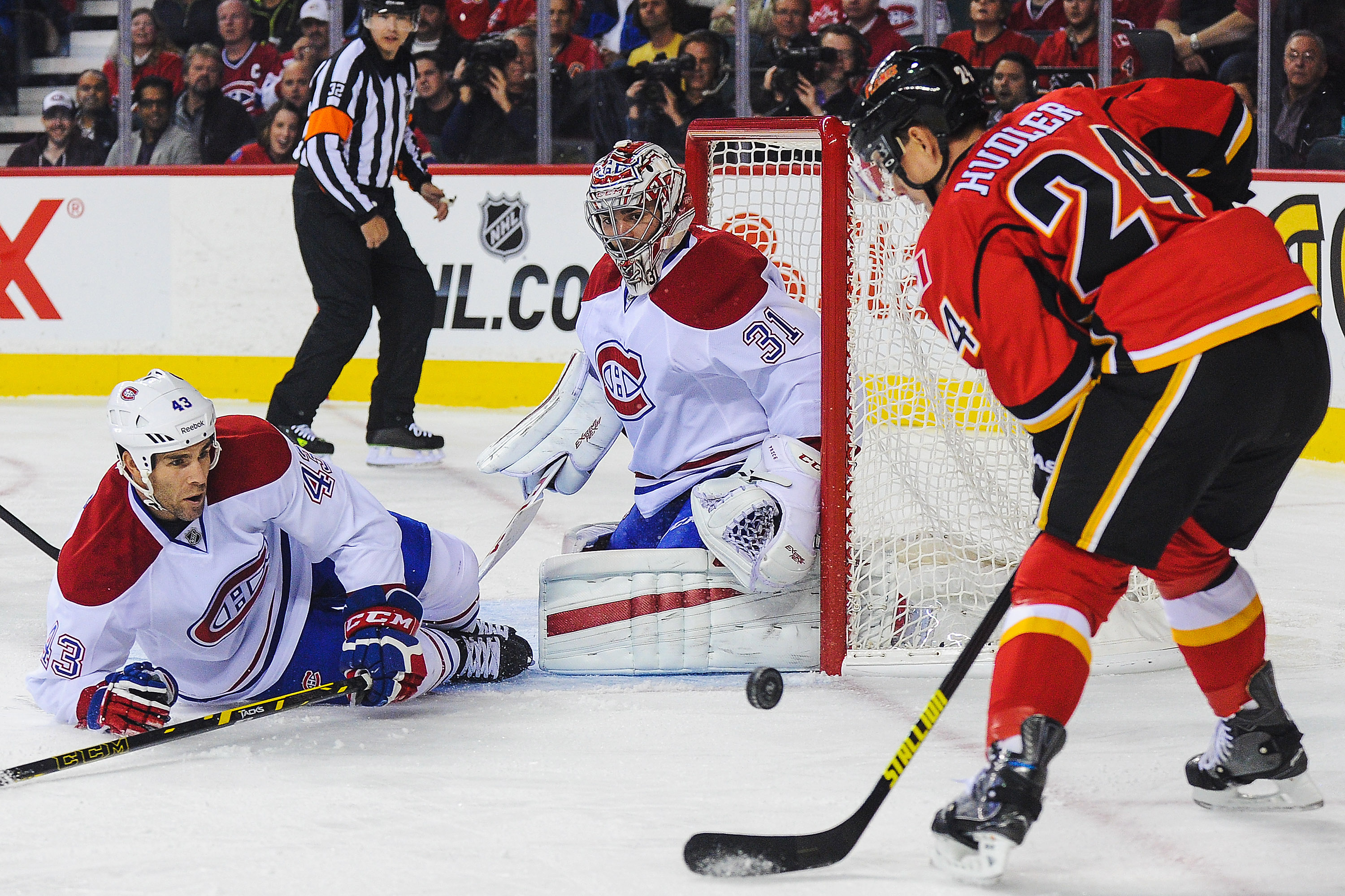 CALGARY, AB - OCTOBER 28: Jiri Hudler #24 of the Calgary Flames takes a shot as Mike Weaver #43 (L) and Carey Price #31 of the Montreal Canadiens defend during an NHL game at Scotiabank Saddledome on October 28, 2014 in Calgary, Alberta, Canada. (Photo by Derek Leung/Getty Images)