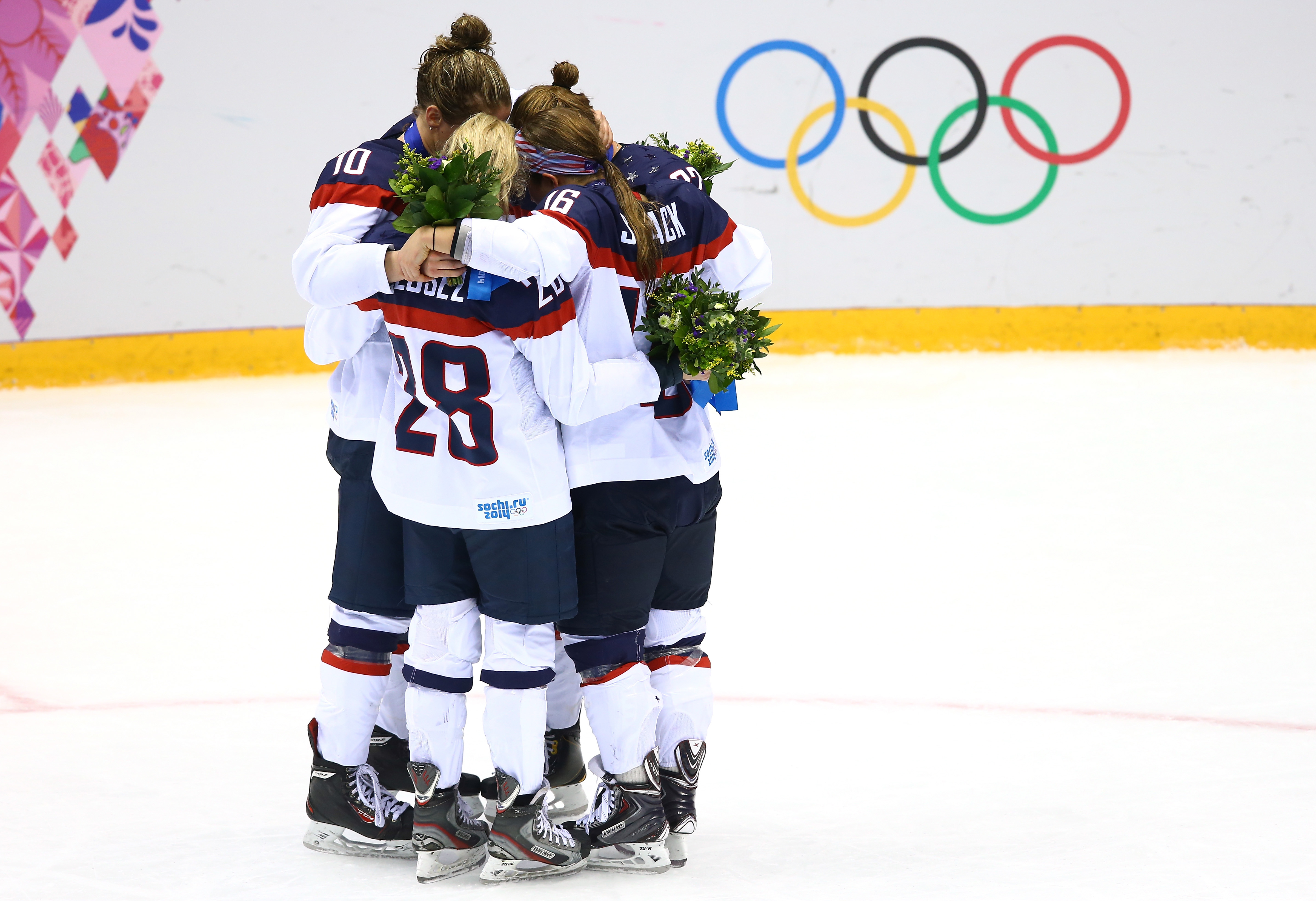 SOCHI, RUSSIA - FEBRUARY 20: Silver medalists Kelli Stack #16, Meghan Duggan #10, Amanda Kessel #28 and Kacey Bellamy #22 of the United States react during the flower ceremony after losing 3-2 to Canada in overtime during the Ice Hockey Women's Gold Medal Game on day 13 of the Sochi 2014 Winter Olympics at Bolshoy Ice Dome on February 20, 2014 in Sochi, Russia. (Photo by Doug Pensinger/Getty Images)