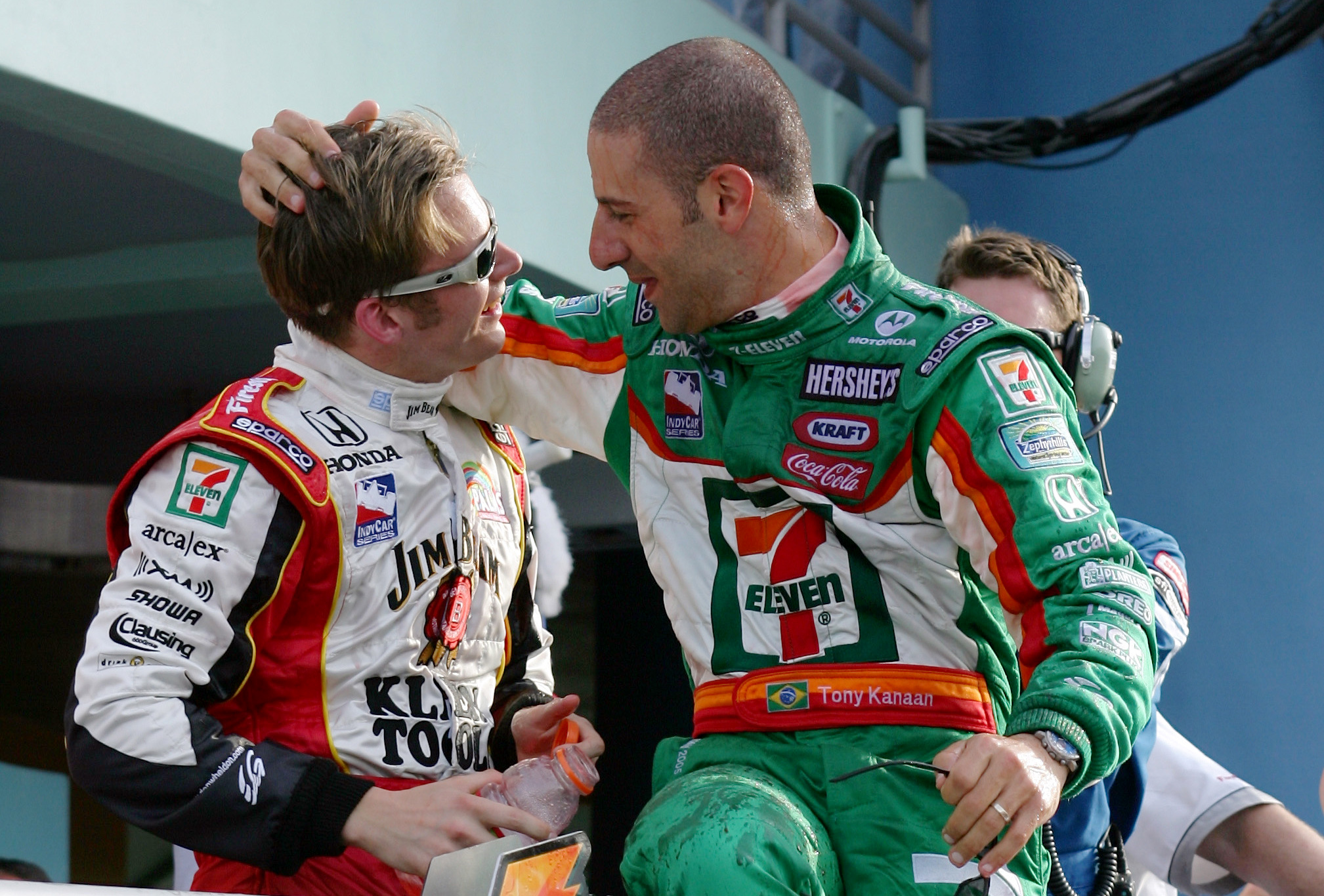 HOMESTEAD, FL - MARCH 6:  Dan Wheldon, driver of the #26 Andretti Green Racing Klein Tools/Jim Beam Honda Dallara, celebrates on the victory podium with teammate Tony Kanaan (R) after winning the IRL IndyCar Series Toyota Indy 300 on March 6, 2005 at the Homestead-Miami Speedway in Homestead, Florida.  (Photo by Robert Laberge/Getty Images)