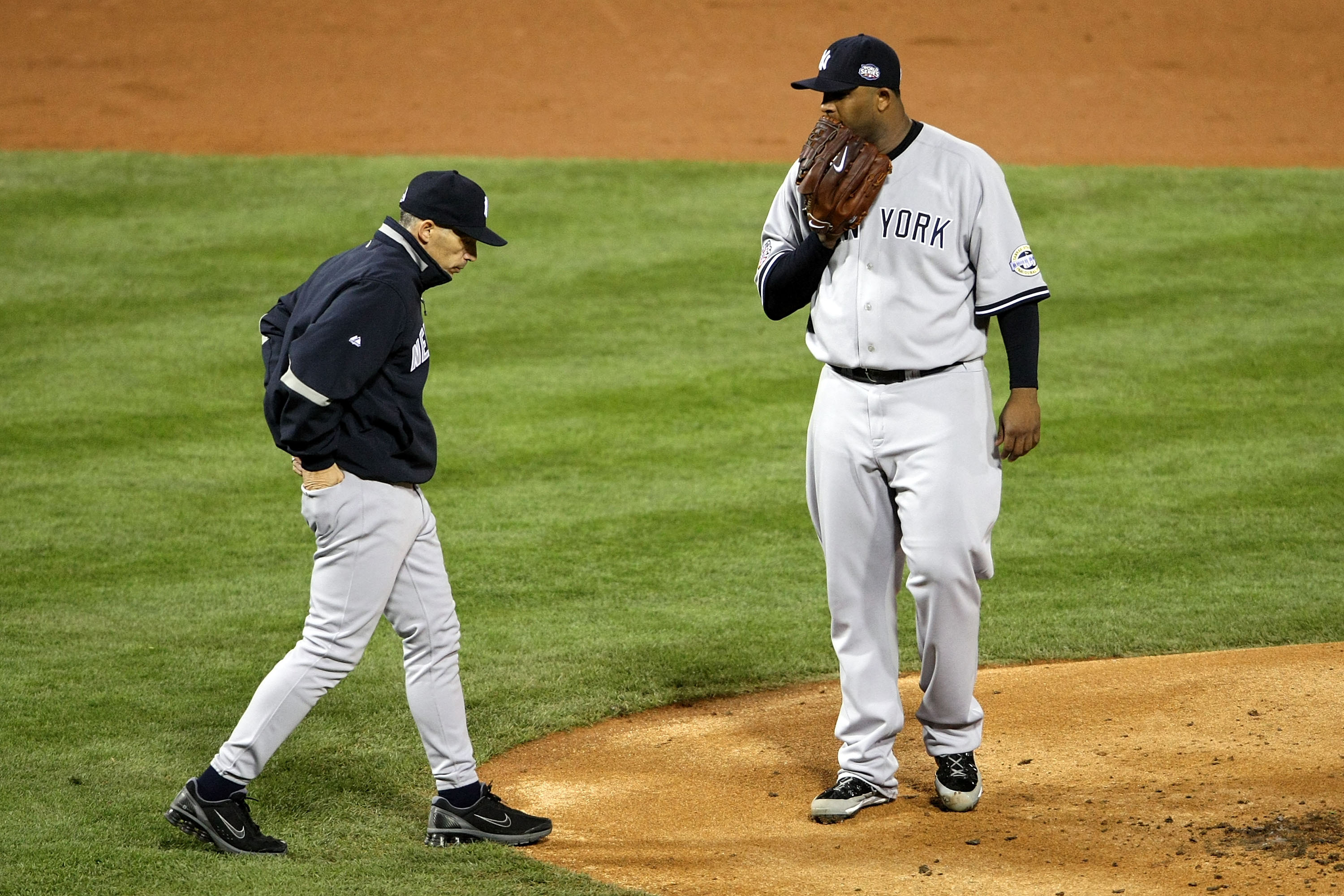 PHILADELPHIA - NOVEMBER 01:  Manager Joe Girardi of the New York Yankees walks out to talk to starting pitcher C.C. Sabathia #52 in the bottom of the first inning against the Philadelphia Phillies in Game Four of the 2009 MLB World Series at Citizens Bank Park on November 1, 2009 in Philadelphia, Pennsylvania.  (Photo by Nick Laham/Getty Images) *** Local Caption *** Joe Girardi;C.C. Sabathia