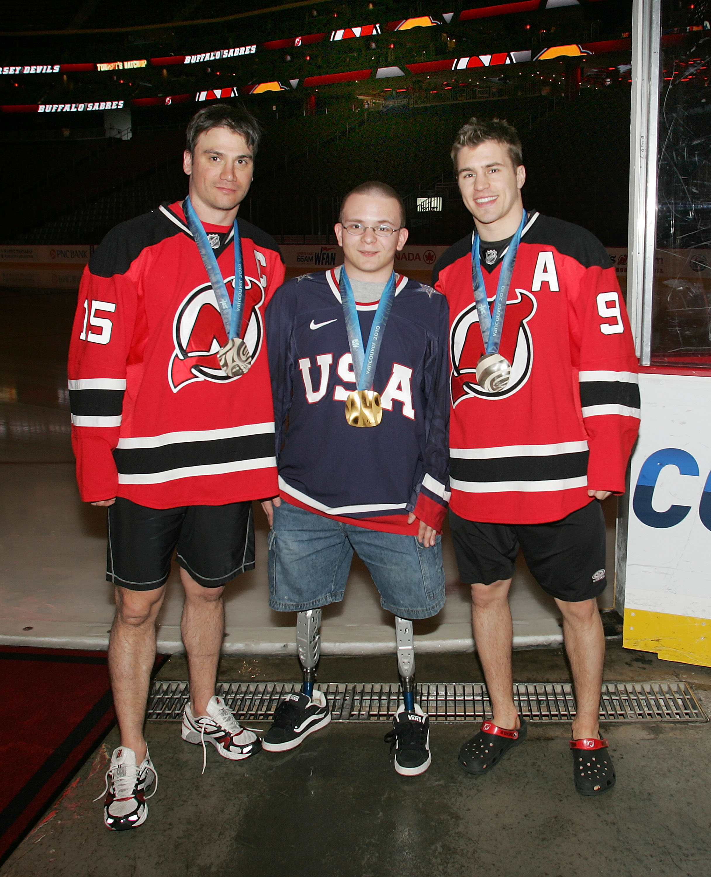 NEWARK, NJ - APRIL 11: Josh Pauls, a member of the gold medal United States paralympic sled hockey team, poses with  Jamie Langenbrunner #15 and Zach Parise #9 of the New Jersey Devils prior to the game against the Buffalo Sabres at the Prudential Center on April 11, 2010 in Newark, New Jersey. (Photo by Andy Marlin/NHLI via Getty Images)