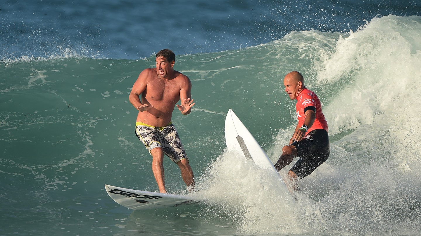 Surf coach Ricky Schaffer almost gets tied up with Kelly Slater prior to Kelly's first heat.