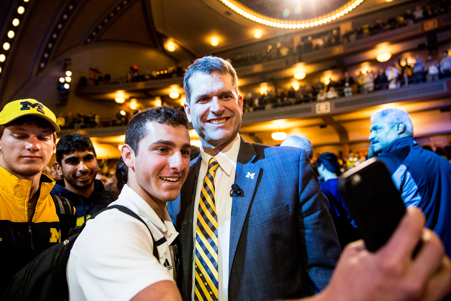 Coach Harbaugh poses for a selfie with a supporter.
