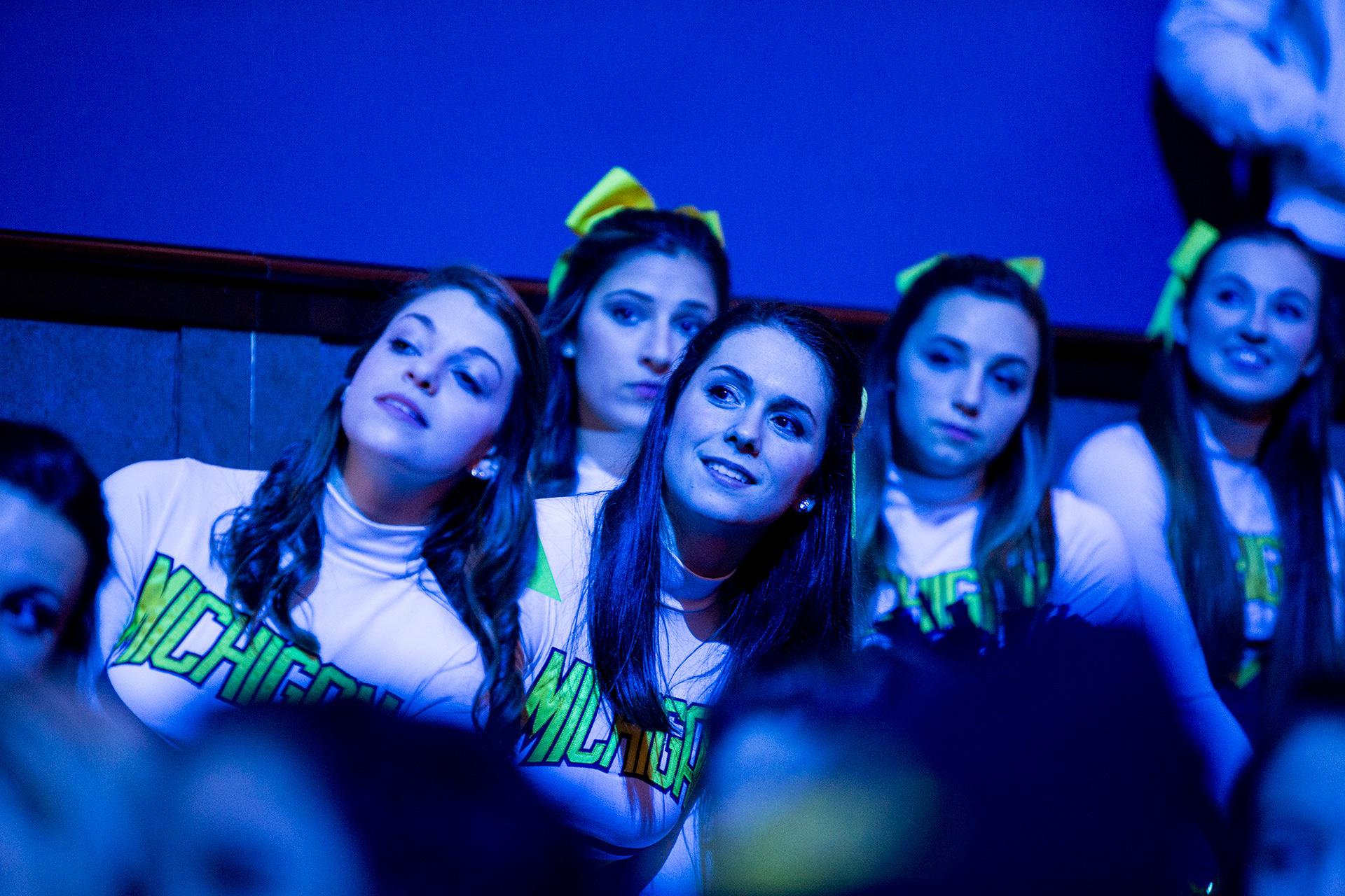 Cheerleaders look on.