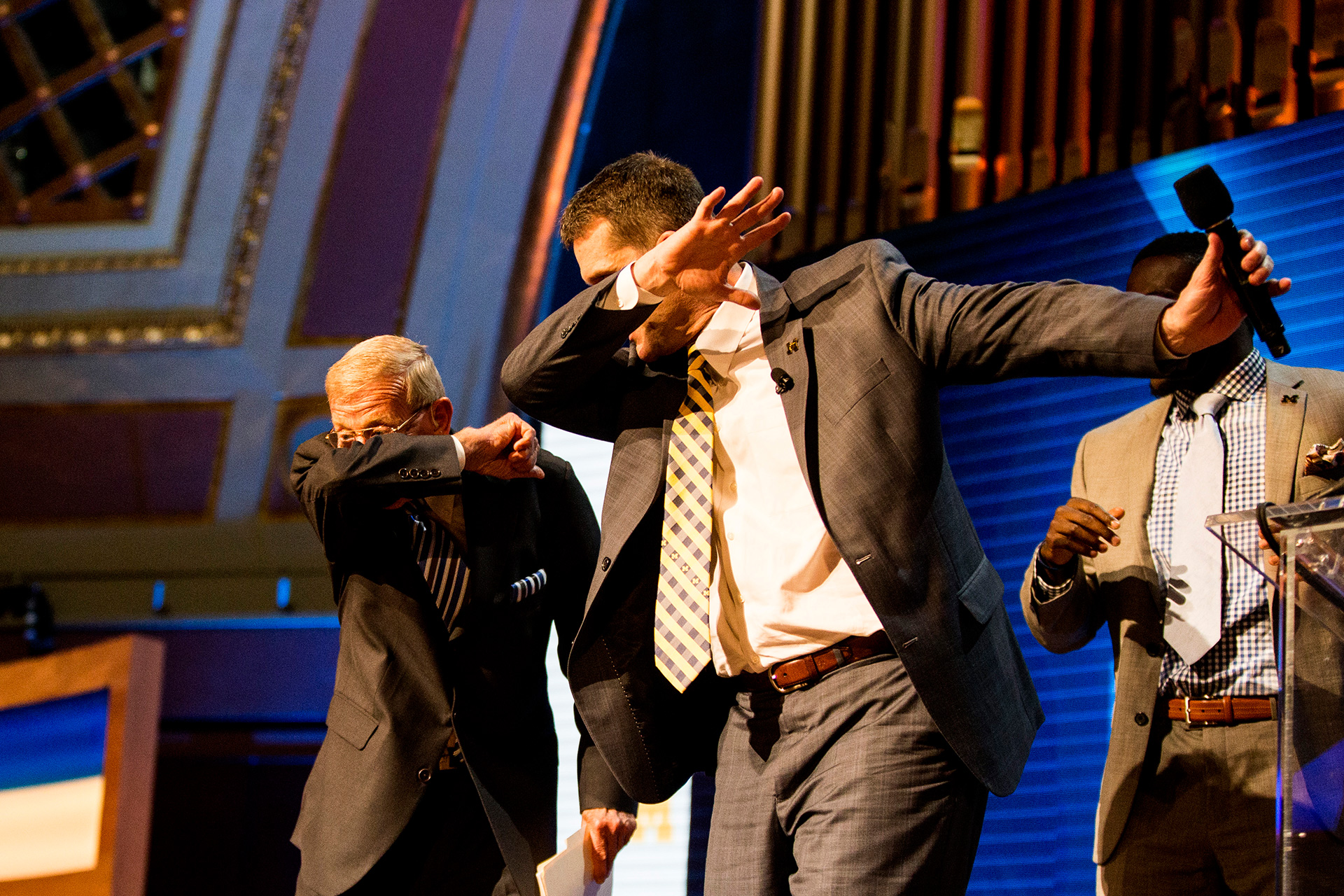 Lou Holtz and Coach Harbaugh dab.