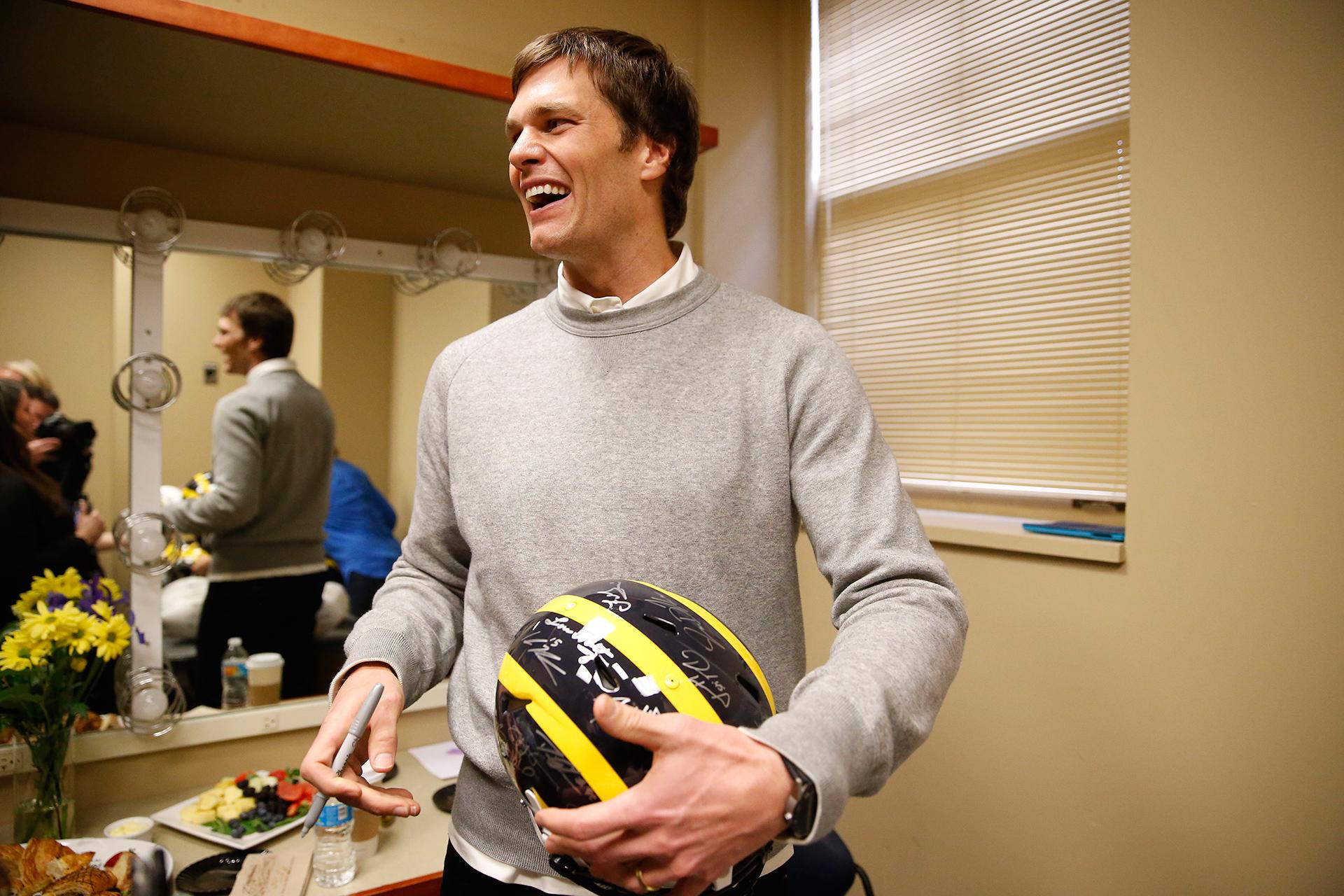Patriots quarterback Tom Brady signs a helmet backstage.