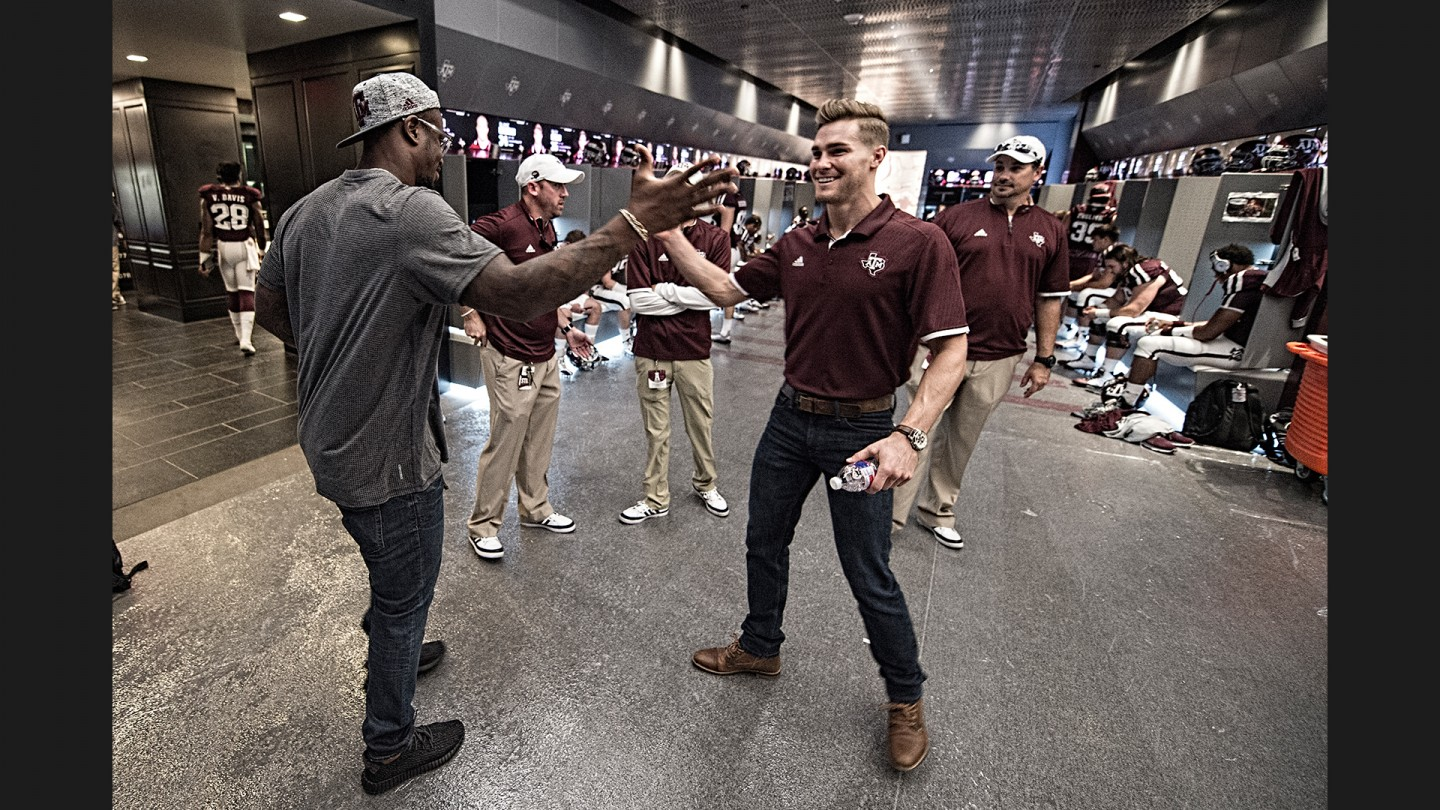 Former Aggies Von Miller and Clay Honeycutt greet each other in the Aggie locker room before the game against Nevada. Miller was enjoying an off weekend in the Denver Broncos schedule after beating the Chiefs on Thursday night. Honeycutt is currently pursuing his masters in Sports Management at A&M.