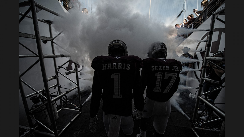Defensive backs De'Vante Harris and Alex Sezer Jr. make their way through the smoke curtain and onto the field.