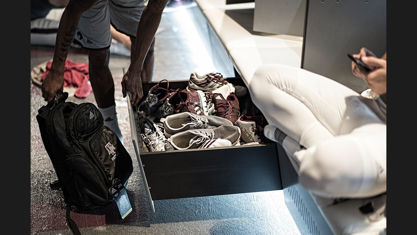 Wide receiver Josh Reynolds looks for a pair of shoes in his locker before pregame warmups against Nevada.