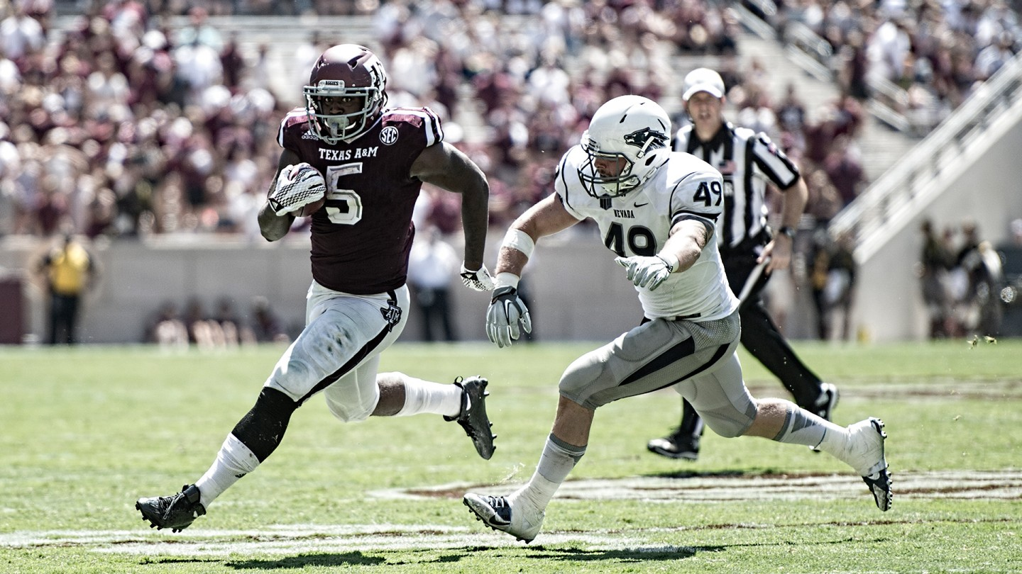 Running back Tra Carson looks to get past a Nevada defender and turn for the end zone during the Aggies' win.