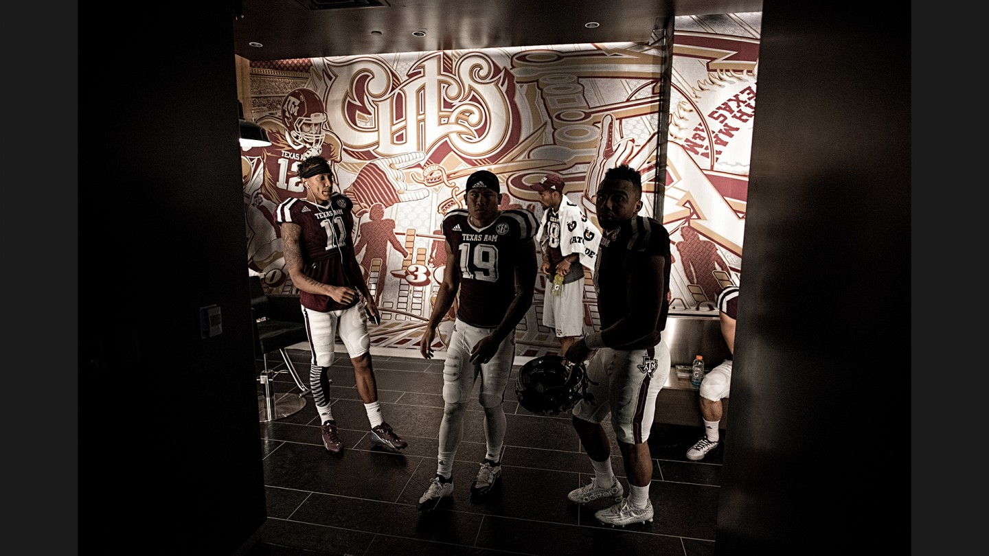 After meeting in the locker room barber shop, Josh Reynolds (11), Jeremy Tabuyo (19) and Christian Kirk (3) of the wide receiving corps head back into the main locker room and get ready to take the field for the second half.