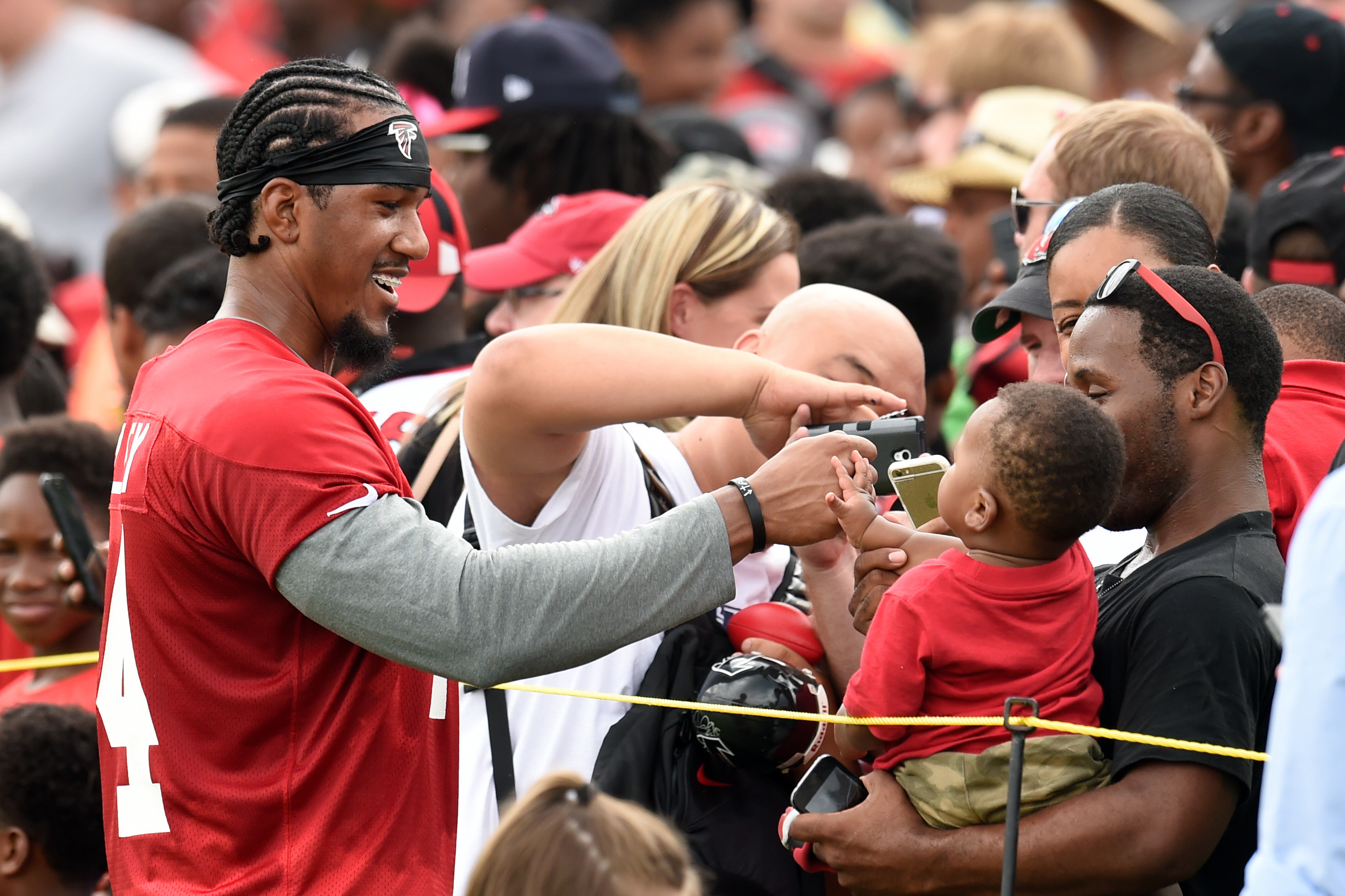 Aug 1, 2015; Atlanta, GA, USA; Atlanta Falcons defensive end Vic Beasley (44) fist bumps with a young fan while signing autographs after practice during training camp at the Flowery Branch Training Facility. Mandatory Credit: Dale Zanine-USA TODAY Sports