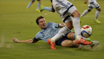 Aug 15, 2015; Kansas City, KS, USA; Sporting KC defender Matt Besler (5) goes in for a slide tackle against the Vancouver Whitecaps FC during the first half at Sporting Park. Mandatory Credit: Peter G. Aiken-USA TODAY Sports