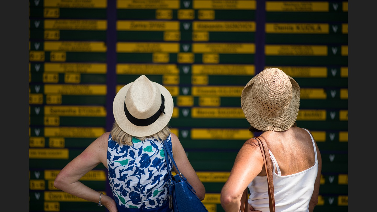 Spectators look at the order of play boards on Day 3.