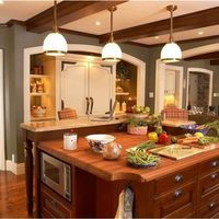 A maplewood finished island with a teak countertop accentuates the warm feeling of this family kitchen.