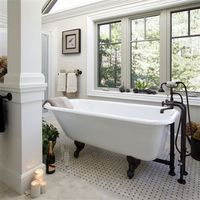 A clawfoot bathtub on a limestone floor positioned next to natural light creates an instant relaxing retreat.