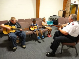 Major Riggs teaching children about guitar playing