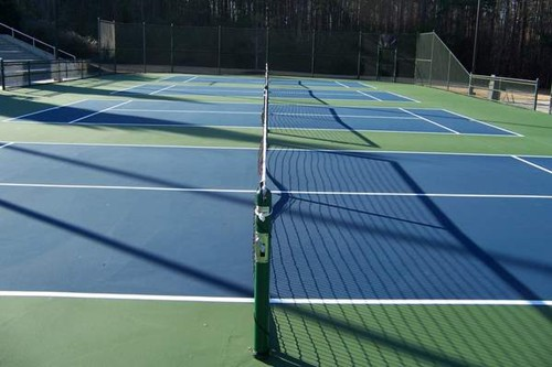 After the playing lines are painted, net posts, nets and center straps are installed.  The courts ar