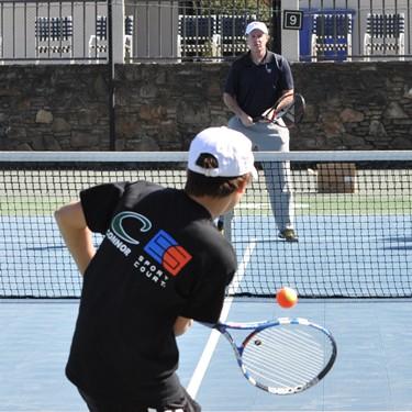 Patrick McEnroe rallies with orange ball.