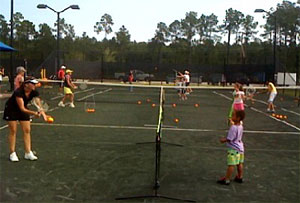 QuickStart Tennis instructors work with beginner children