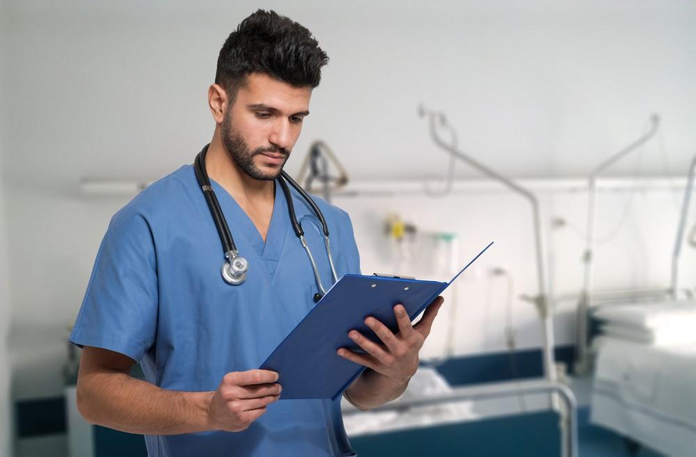 A male nurse reads a patient chart.