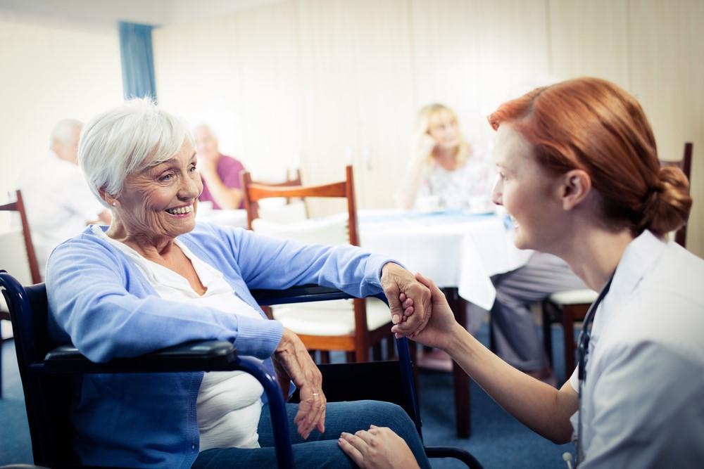 A female nurse talks to a woman in a wheelchair in a nursing home.