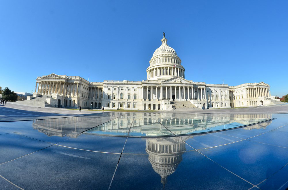 The U.S. capitol building and its reflection on the sidewalk.