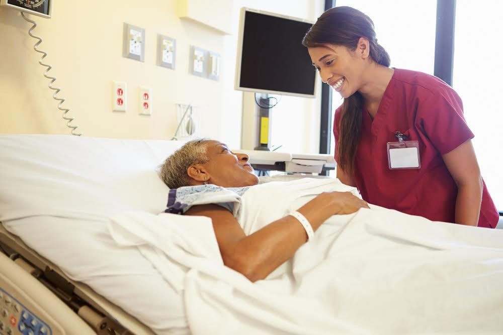 Nurse speaks to a patient lying in a hospital bed