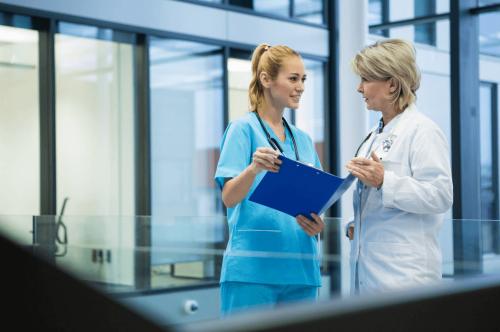 An FNP speaks with a nurse.